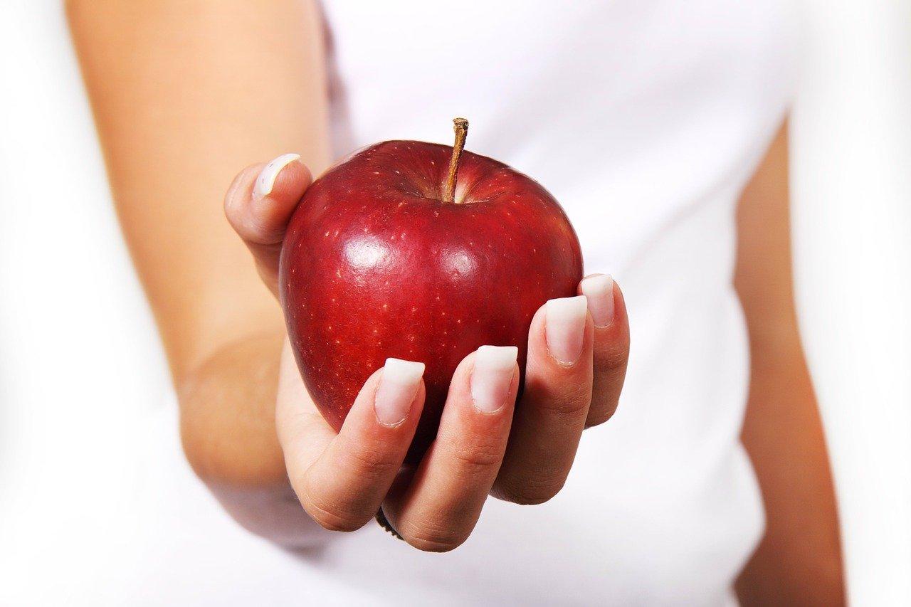 皮付きのリンゴを持っている人