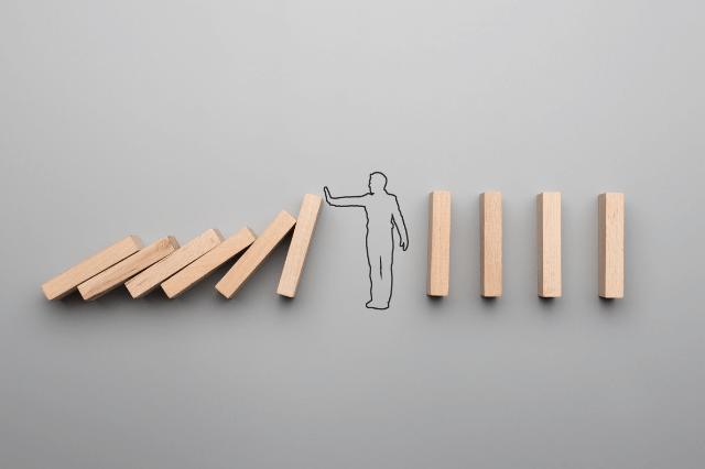 倒れるドミノを止める人のイラスト